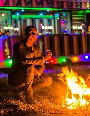A smartly dressed man at a campfire, with a brightly lit bar behind him.